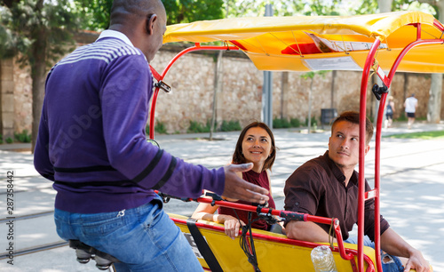 Fotografija Active girl with boyfriend traveling on rickshaw