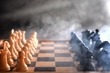 Chess figures on a grey background with smoke and fog. Selective focus