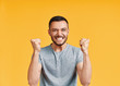 Happy man celebrating his success with winner gesture on yellow background