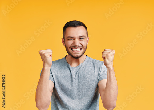 Obraz na plátně Happy man celebrating his success with winner gesture on yellow background