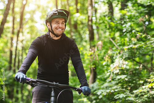 Joyful male bicyclist cycling in mountain forest Фотошпалери