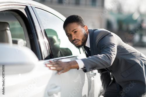 Foto  The final check. Afro man examining new car at dealership