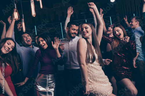 Obraz Nice-looking attractive lovely glamorous shine cheerful cheery glad positive elegant stylish diverse ladies and gentlemen having fun festal occasion in modern fashionable luxury place indoors - fototapety do salonu