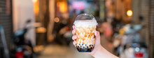 Young Girl Is Holding And Showing A Cup Of Brown Sugar Flavored Tapioca Pearl Bubble Milk Tea In Night Market Of Taiwan Background, Close Up, Bokeh
