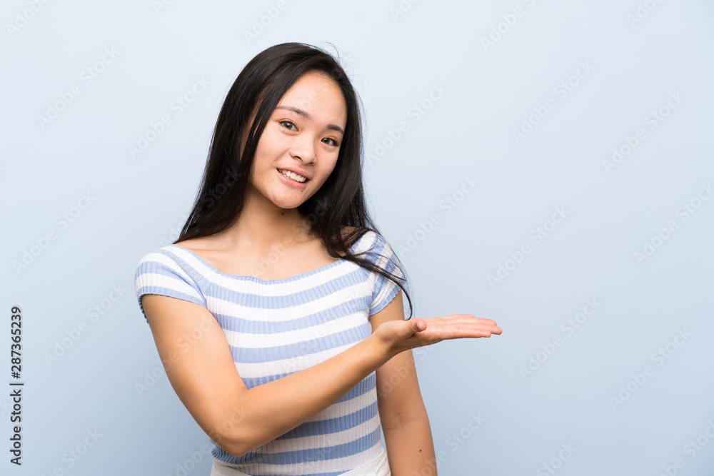 Fototapety, obrazy: Teenager asian girl over isolated blue background extending hands to the side for inviting to come