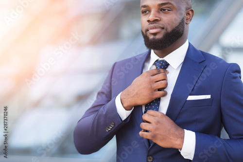 Photo Young Black Businessman Adjusting Necktie In Urban Area