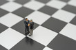 canvas print picture - Miniature 2 people businessmen Shake hands standing on a chessboard with a chess piece on the back Negotiating in business. as background business concept and strategy concept with copy space.