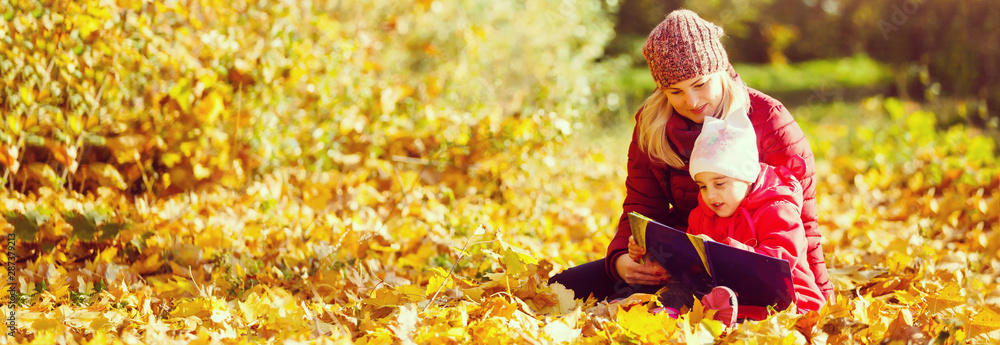Fototapety, obrazy: mother teaching daughter in autumn park, Mother teaching daughter to read.