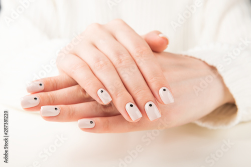 hand with beige manicure with dots nail design.. #287381220