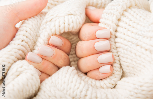 pastel beige Nails holding knitted wool material #287381682
