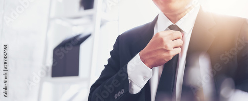 Fotografiet  Businessman in black suit and adjusting necktie on office.