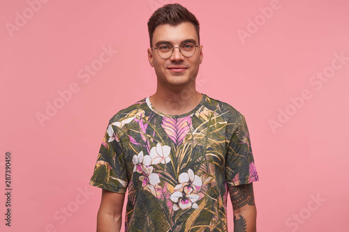 Indoor portrait of handsome young guy with tattoos wearing glasses and flowered Canvas Print
