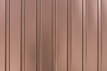 Metal Wall Siding Texture. Ribbed, Striped Surface. Shiny Metallic Cladding On Wall. Brown Background. Reflected Light Cover.