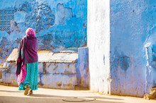 Stunning View Of An Unidentified Woman Dressed In The Traditional Indian Sari Walking Through The Narrow Streets Of The Blue City Of Jodhpur During A Beautiful Sunset. Jodhpur, Rajasthan, India.