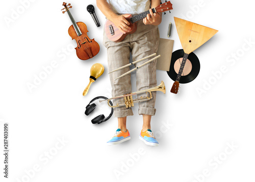 Young man sits and plays guitar among musical instruments