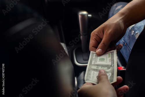 Photo Hand giving dollar banknote to driver