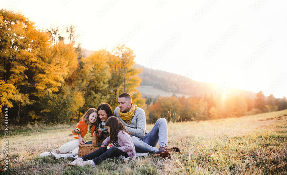 Fototapeta A young family with two small children having picnic in autumn nature at sunset.