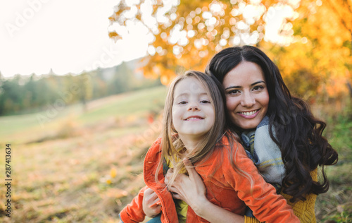 A portrait of young mother with a small daughter in autumn nature at sunset. - 287413634