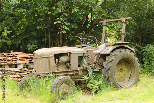Fototapety, obrazy: old and rusty tractor surrounded by grass and trees