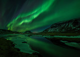 Aurora borealis (Northern Lights) reflected in partially frozen lake, North Snaefellsnes, Iceland