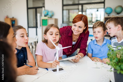 A group of small school kids with teacher in class learning about environment Canvas Print