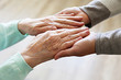 canvas print picture - Mature female in elderly care facility gets help from hospital personnel nurse. Senior woman w/ aged wrinkled skin & care giver, hands close up. Grand mother everyday life. Background, copy space.