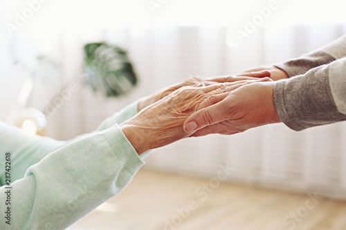 Photo Mature female in elderly care facility gets help from hospital personnel nurse