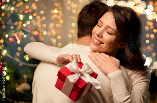 winter holidays and people concept - happy couple with christmas gift hugging at home - 287423230