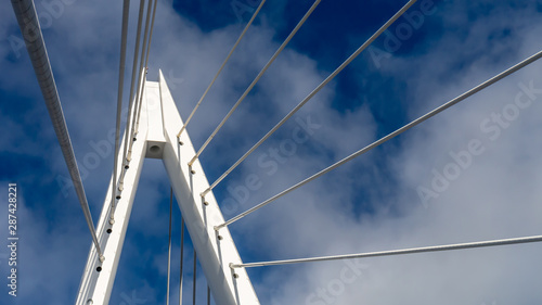 Photo Top spire of the Northern Spire bridge in Sunderland, showing cables and the white metal apex structure against the blue sky