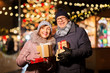 Leinwanddruck Bild - love, winter holidays and people concept - happy senior couple with gift at christmas market on town hall square in tallinn, estonia