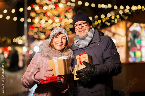 Foto auf Gartenposter Lineale Wachstum love, winter holidays and people concept - happy senior couple with gift at christmas market on town hall square in tallinn, estonia