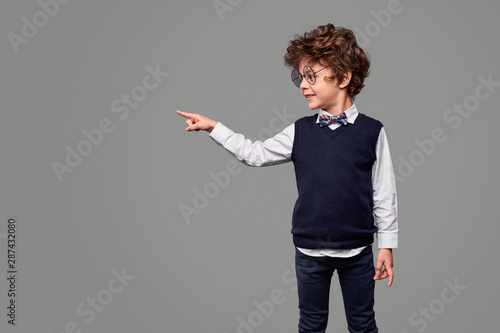 Photo Smiling schoolboy pointing aside