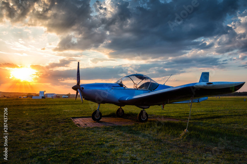Obraz na plátne A small sports airplane parked at the airfield at scenic sunset