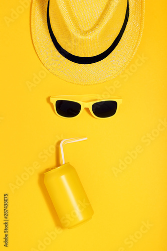 Aluminum can with sunglasses and hat on yellow background. Minimalism concept