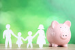 canvas print picture - Family figures with piggybank on green background