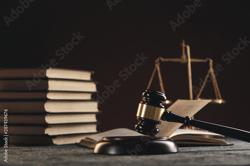 Canvas Print Law concept - Open law book with a wooden judges gavel on table in a courtroom or law enforcement office on black background
