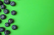 canvas print picture - Tasty ripe blueberries on green background, flat lay with space for text