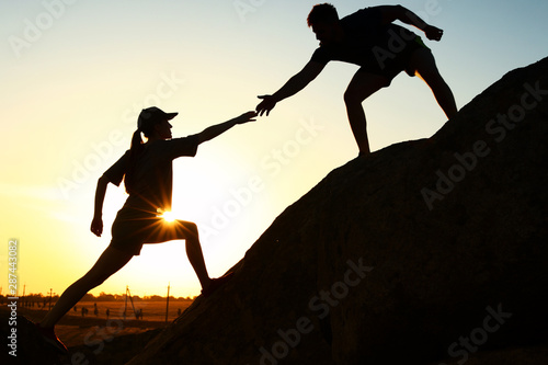 Hiker helping friend outdoors at sunset. Help and support concept Wallpaper Mural