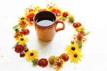 Cup Of Tea In Middle Of Circle Flower Composition On A Wooden White Background