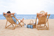 Happy young couple sitting on deck chairs at sea beach