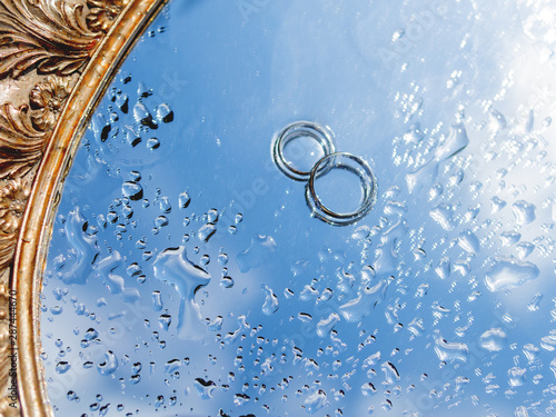 Obraz Pair of wedding rings on wet mirror surface with blue sky reflection. Close up photo with traditional jewelry of bride and groom. - fototapety do salonu
