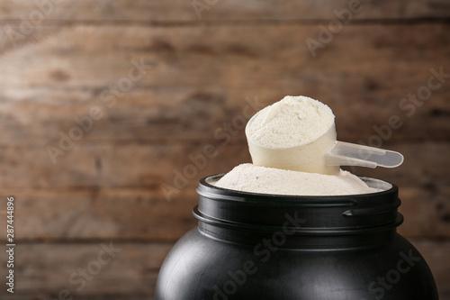 Carta da parati  Black jar with measuring scoop of protein powder against wooden background