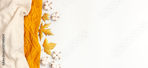 Flat lay autumn composition. Knitted woolen light beige and yellow orange sweater or plaid, golden dry leaves, cotton flowers on white background top view copy space. Autumn, fall concept