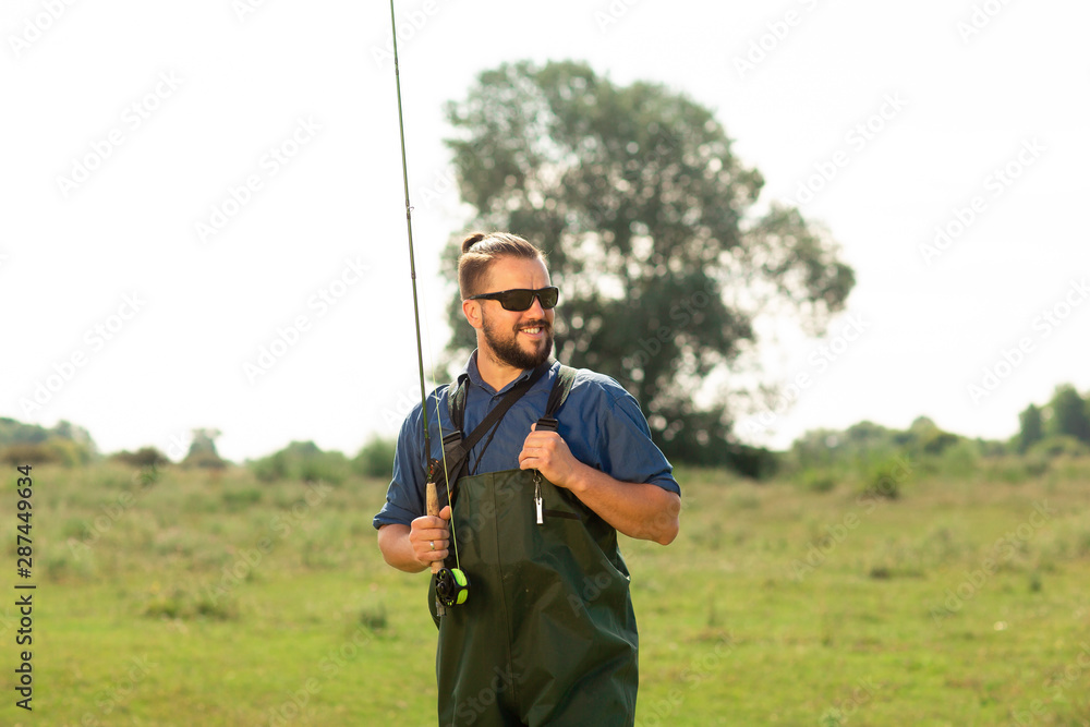 Fototapety, obrazy: Happy fisherman in black glasses and a special suit poses in the nature. He holds his fishing rod in his hands