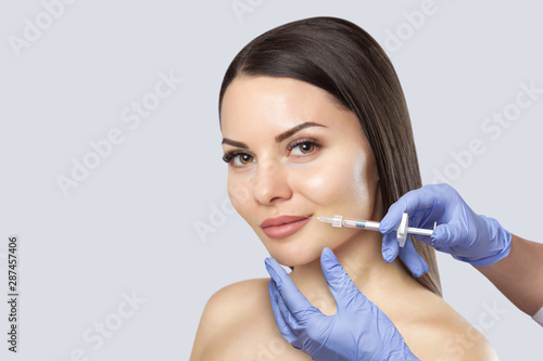 There is a woman, who is making the Lips augmentation procedure  in a beauty salon Wallpaper Mural