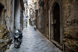 Fototapeta Uliczki - Scenic view of typical narrow alleyway lined with scooters and laundry lines in the Medieval Centro Storico of Naples, Italy