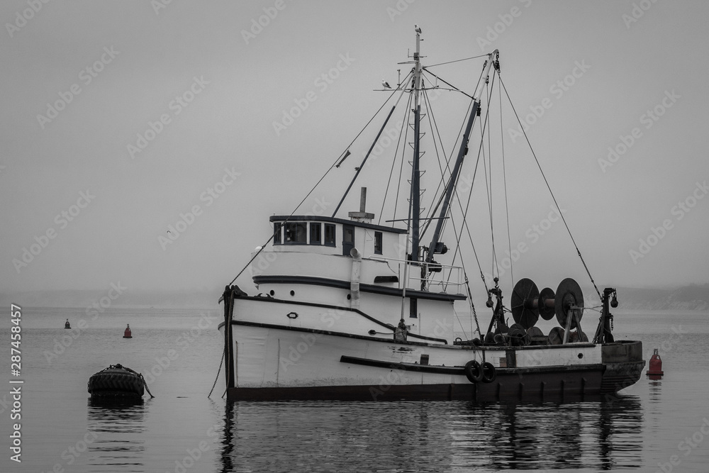 Fototapeta Black and white image of an old fishing boat moored in the Monterey Harbor and Marina along the Monterey Bay of central California.