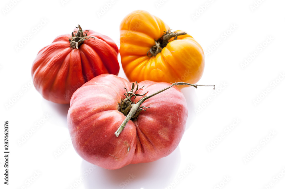 Fototapety, obrazy: Three tomatoes of different colors and shapes on a white background. Isolated composition. Copy space