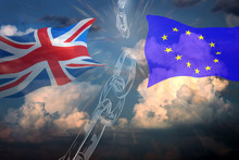 Brexit Concept. UK Flag And EU Flag Waving In The Wind Against Cloudy Sky Background