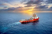 Supply Vessel Transport Cargo For Rig Platform Offshore At Sunset.